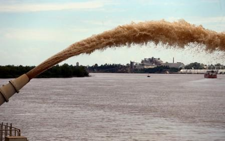 FILE PHOTO: A dredging boat sprays sand at the shore on the Parana river near Rosario, Argentina