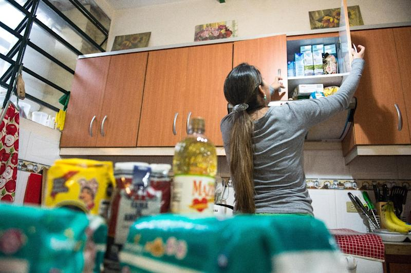 A woman checks food stocks on February 2, 2015 in Caracas, Venezuela where the economic crisis is proving ever more painful (AFP Photo/Federico Parra )