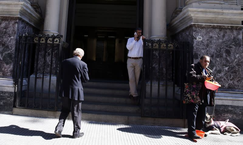Blind man begs for money at the front entrance of Argentina's Central Bank in Buenos Aires' financial district