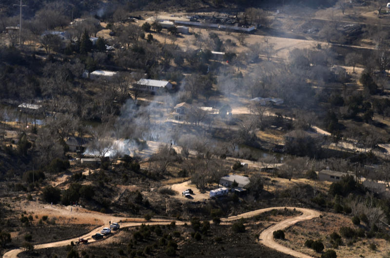 A building in the Lake Tanglewood and Palisades area of Amarillo, Texas smolders Monday, Feb. 28, 2011. Wind-driven wildfires have scorched some 190 square miles in the state. (AP Photo/The Amarillo Globe News, Stephen Spillman)