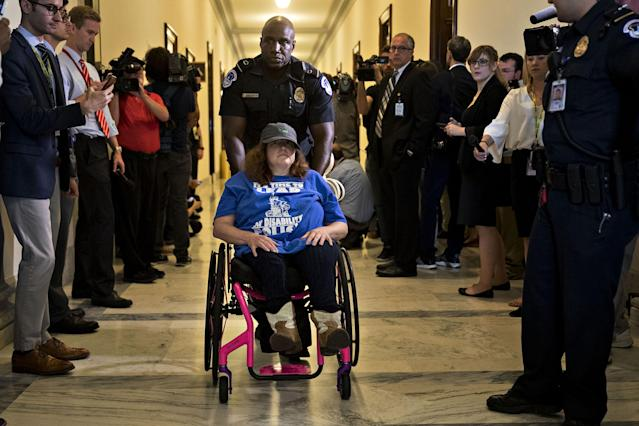 <p>A demonstrator in a wheelchair protesting cuts to Medicaid is led from the office of Senate Majority Leader Mitch McConnell by a U.S. Capitol police officer at the Russell Senate Office building in Washington, D.C., U.S., on Thursday, June 22, 2017. (Photo: Andrew Harrer/Bloomberg via Getty Images) </p>
