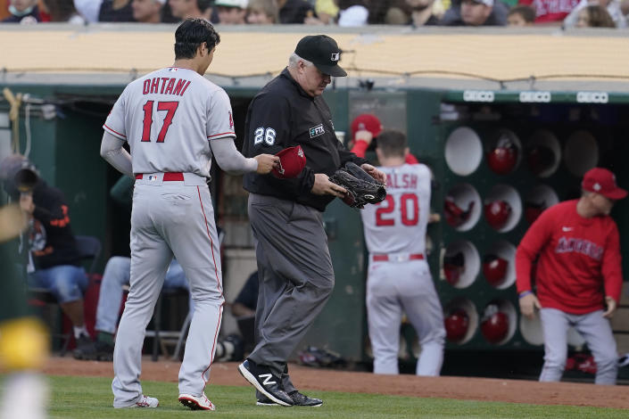 Umpire Bill Miller (26) inspects the glove of Los Angeles Angels pitcher Shohei Ohtani (17) during the third inning of a baseball gam against the Oakland Athletics in Oakland, Calif., Monday, July 19, 2021. (AP Photo/Jeff Chiu)