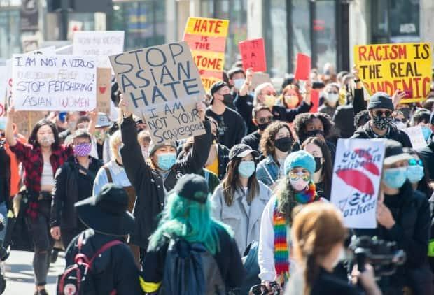 Hundreds of people marched through downtown Montreal on Sunday to denounce anti-Asian racism and honour the victims of shootings in Atlanta earlier in the week. (Graham Hughes/The Canadian Press - image credit)
