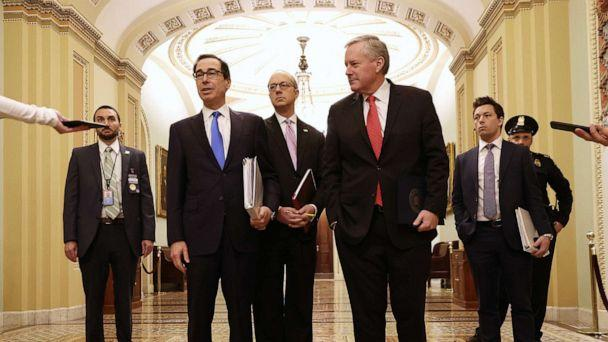 PHOTO: Treasury Secretary Steven Mnuchin talks briefly with reporters after arriving at the Capitol with White House Director of Legislative Affairs Eric Ueland and White House Chief of Staff Mark Meadows, March 24, 2020 in Washington. (Chip Somodevilla/Getty Images)