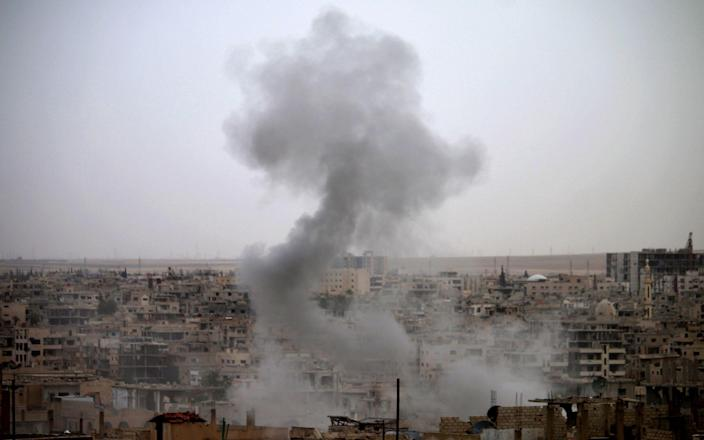 Smoke rises from buildings in a rebel-held neighbourhood of Daraa in southern Syria following reported shelling - AFP