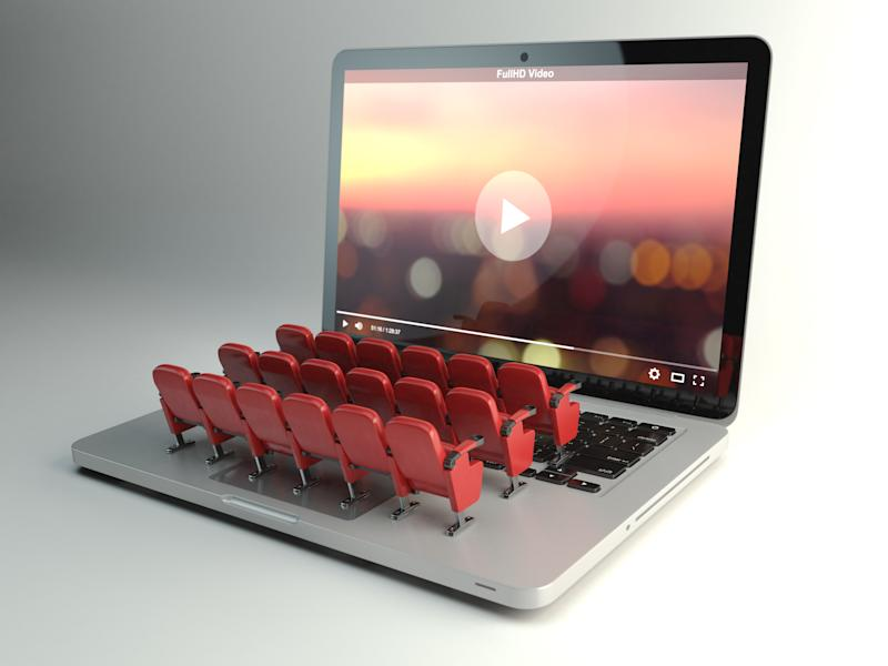 Tiny, toy movie theater seats sit on an open laptop's keyboard.
