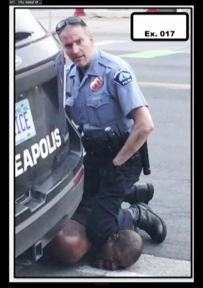 "In this image from video provided by Darnella Frazier, Minneapolis Police Officer Derek Chauvin kneels on the neck of George Floyd in Minneapolis on Monday, May 25, 2020. The former Minneapolis police officer charged with killing Floyd went on trial Monday, March 29, 2021. For jurors at Chauvin's murder trial, the enduring image of the defendant is his impassive expression as he gazed at the teenager filming his knee pinning Floyd's neck – what the girl called his ""cold"" and ""heartless"" stare. (Darnella Frazier via AP)"