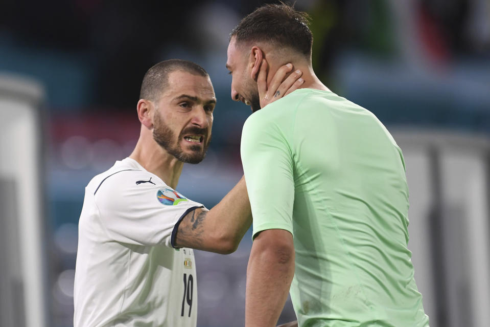 Italy's Leonardo Bonucci, left, hugs Italy's goalkeeper Gianluigi Donnarumma after a Euro 2020 soccer championship quarterfinal match between Belgium and Italy at the Allianz Arena in Munich, Germany, Friday, July 2, 2021. (Andreas Gebert/Pool Photo via AP)