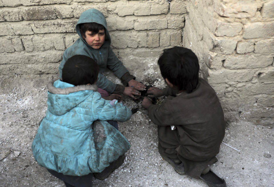 Internally displaced boys warm themselves near a fire outside their temporary home in the city of Kabul, Afghanistan, Wednesday, Dec. 30, 2020. Save the Children has warned that more than 300,000 Afghan children face freezing winter conditions that could lead to illness, in the worst cases death, without proper winter clothing and heating. (AP Photo/Rahmat Gul)
