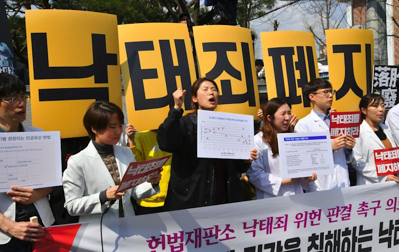 """South Korean women's rights activists hold a rally against the abortion ban outside the Constitutional Court in Seoul on April 11. The yellow placards read """"Abolish punishment for abortion."""" (Photo: JUNG YEON-JE via Getty Images)"""