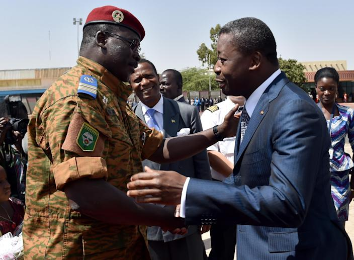 President Faure Gnassingbe of Togo (R) is greeted by Burkina Faso's army-appointed leader Lieutenant-Colonel Isaac Zida (L) at Ouagadougou airport on November 11, 2014 (AFP Photo/Issouf Sanogo)