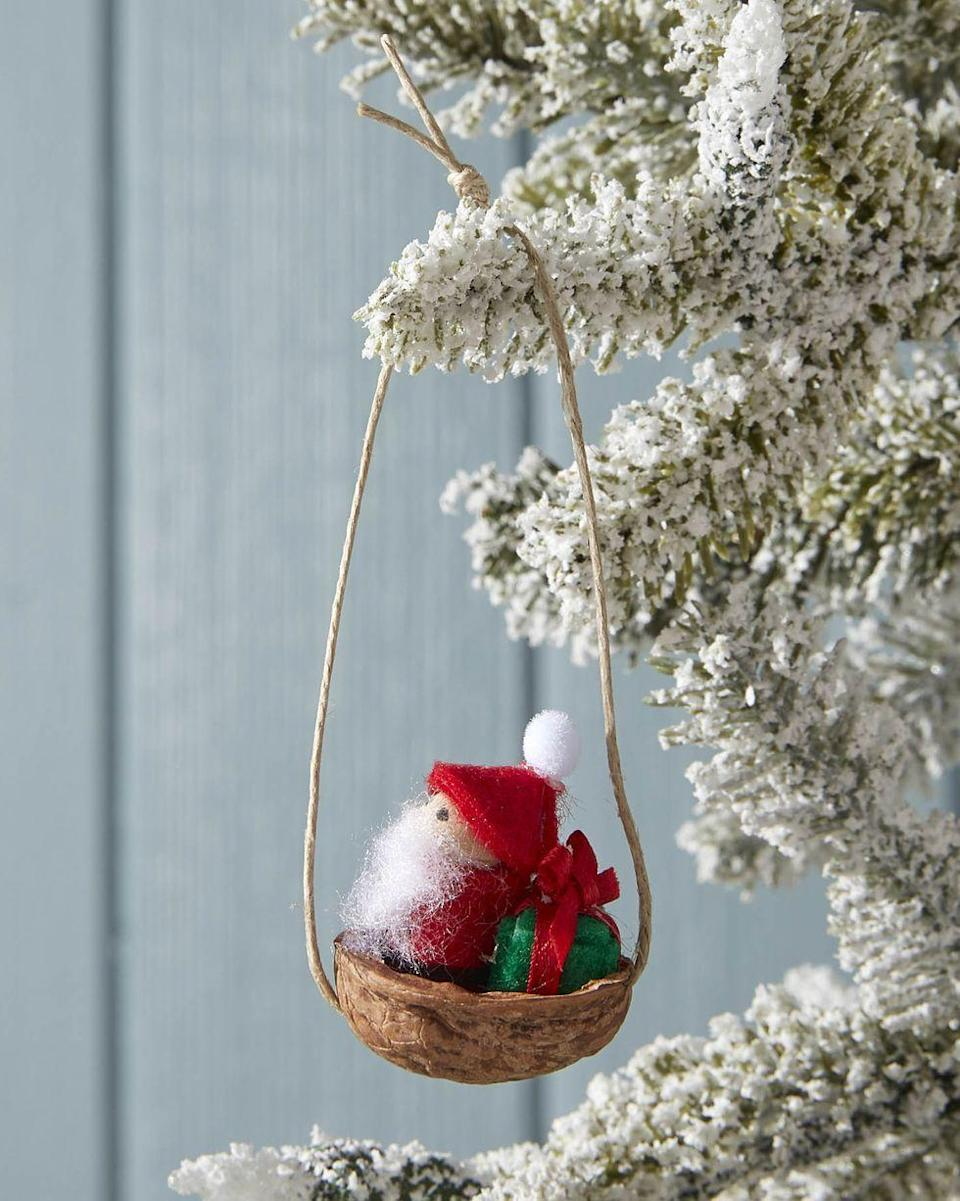 """<p>No matter who you give this ornament to, they're sure to go nuts for the adorbs walnut shell sleigh.</p><p><strong>To make:</strong> Draw eyes on the face of a small wooden peg doll with a fine-tip black marker. Wrap the body of the doll in red felt; holding it in place with hot glue. Create a small hat from red felt, gluing it to the doll's head with hot glue. Attach a mini pom pom to the hat. Cover a mini wooden cube in green felt, holding it in place with hold glue. Tie a ribbon around the present. Drill small holes on either end of half of a walnut shell. Thread a piece of thin twine through each hole, securing it on the inside of the shell with hot glue. Knot the twine at the top for hanging. Use hot glue to secure Santa and the present in the shell.</p><p><a class=""""link rapid-noclick-resp"""" href=""""https://www.amazon.com/dp/B00WQDTTCE?tag=syn-yahoo-20&ascsubtag=%5Bartid%7C10050.g.645%5Bsrc%7Cyahoo-us"""" rel=""""nofollow noopener"""" target=""""_blank"""" data-ylk=""""slk:SHOP MINI WOODEN PEG DOLLS"""">SHOP MINI WOODEN PEG DOLLS</a></p>"""
