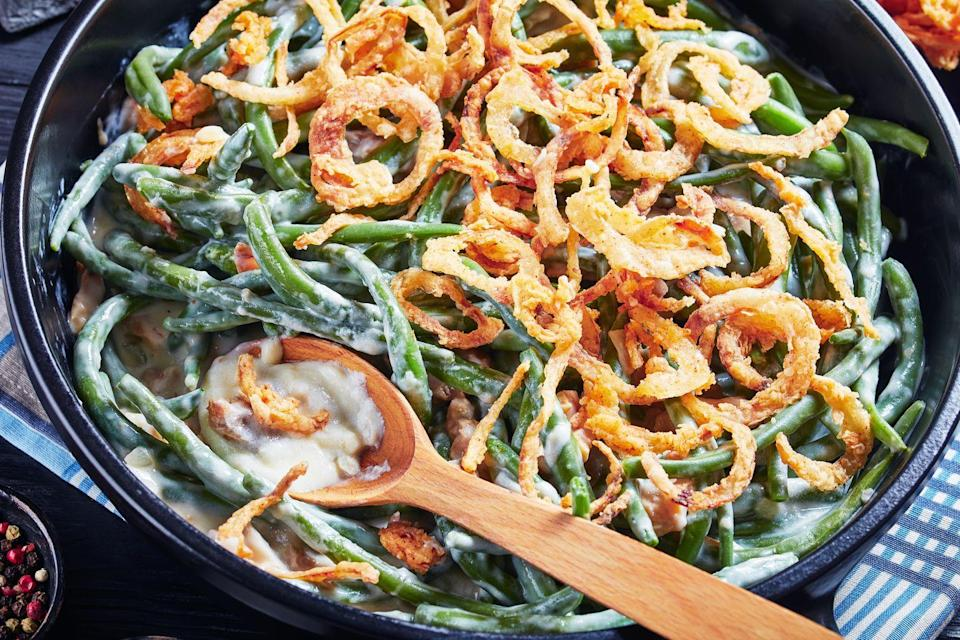 """<p>Green beam casserole, a mix of canned soup, frozen green beans, and fried onions, is not everyone's favorite, yet it remains a holiday staple. The dish was <a href=""""https://www.history.com/news/the-origins-of-the-mysterious-gren-bean-casserole"""" rel=""""nofollow noopener"""" target=""""_blank"""" data-ylk=""""slk:created in 1955"""" class=""""link rapid-noclick-resp"""">created in 1955</a> by Campbell's employee Dorcas Reilly, who mixed Campbell's Cream of Mushroom soup with the frozen veggie, then added fried onions for texture and color. It became immediately popular. </p>"""