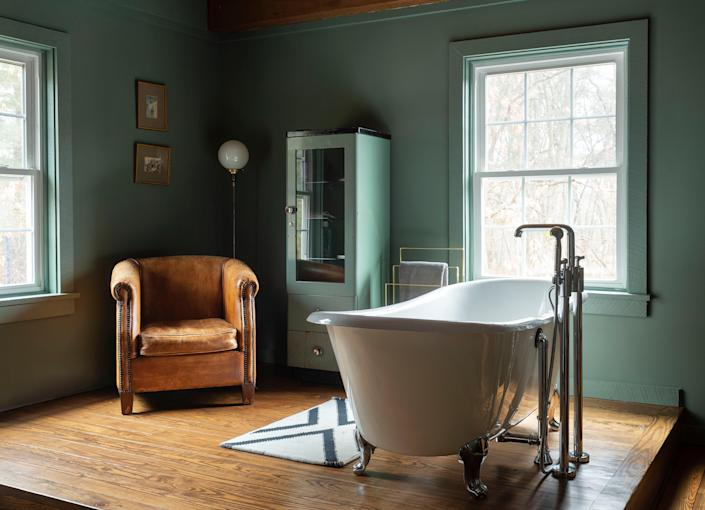 AFTER: Originally a small upstairs bedroom, this room was combined with a bathroom to create a bathing space and dressing room with a fireplace (not shown) for cozy mornings. The tub was existing to the house and refinished and fitted with Waterworks fixtures. The room was painted in Farrow & Ball's Green Smoke, creating a beautiful dark contrast to the bright nature seen through the windows.