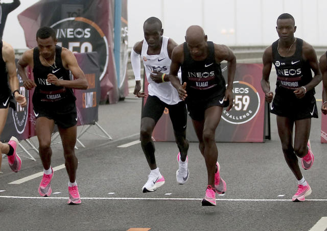 Marathon runner Eliud Kipchoge from Kenya, white vest, and his first pacemaking team leave the start line on Reichsbrucke during the INEOS 1:59 Challenge attempt to run a sub two-hour marathon in Vienna, Austria, Saturday, Oct. 12, 2019. (AP Photo/Ronald Zak)