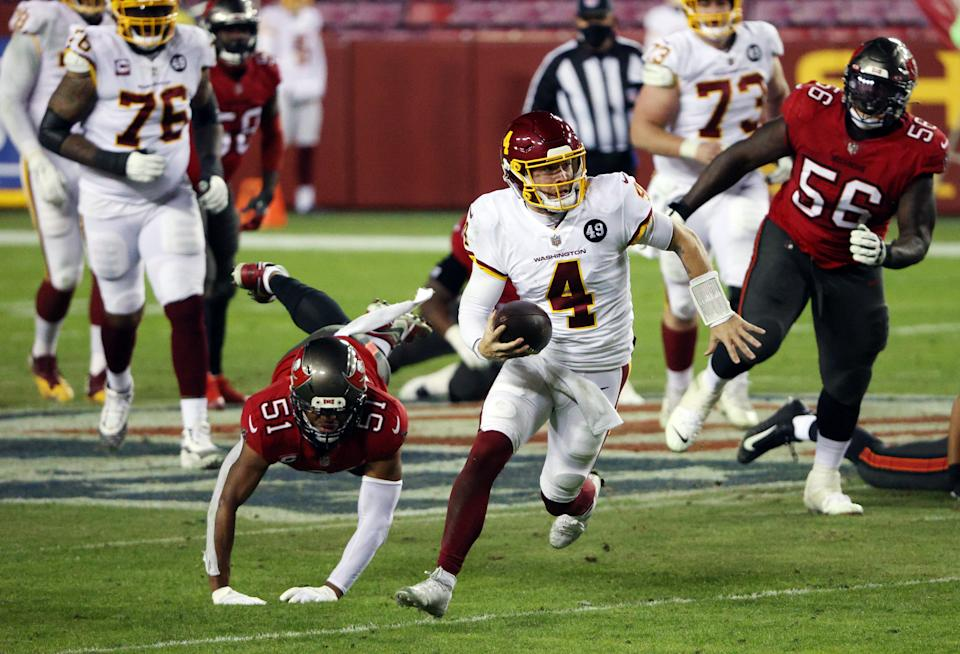 LANDOVER, MARYLAND - JANUARY 09:  Quarterback Taylor Heinicke #4 of the Washington Football Team scrambles during the 3rd quarter of the game against the Tampa Bay Buccaneers at FedExField on January 09, 2021 in Landover, Maryland. (Photo by Patrick Smith/Getty Images)