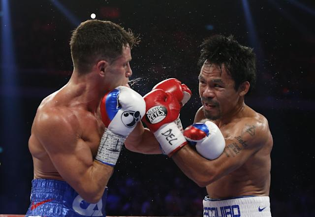 WBO welterweight champion Manny Pacquiao, right, of the Philippines exchanges punches with WBO junior welterweight champion Chris Algieri of the United States during their welterweight boxing title fight at the Venetian Macao in Macau, Sunday, Nov. 23, 2014. (AP Photo/Kin Cheung)