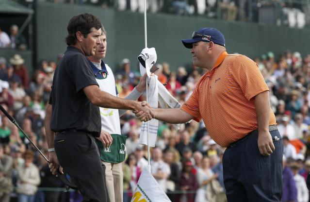Kevin Stadler, right, winner of the Phoenix Open golf tournament, shakes hands with Bubba Watson on the 18th green after the final round Sunday, Feb. 2, 2014, in Scottsdale, Ariz. (AP Photo/Ross D. Franklin)