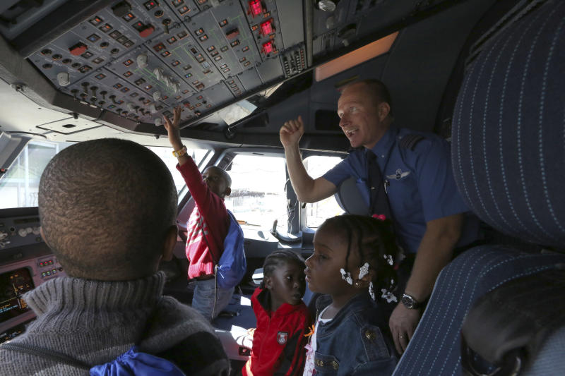 Captain Paul Bruder, right, show a group of children the cockpit, Saturday, Sept. 21, 2013 while the aircraft was parked on the tarmac at JFK airport in New York. Dozens of families with children with autism have practiced air travel at New York's Kennedy International Airport. JetBlue Airways and the nonprofit Autism Speaks held the practice run for families at JFK on Saturday. (AP Photo/Mary Altaffer)