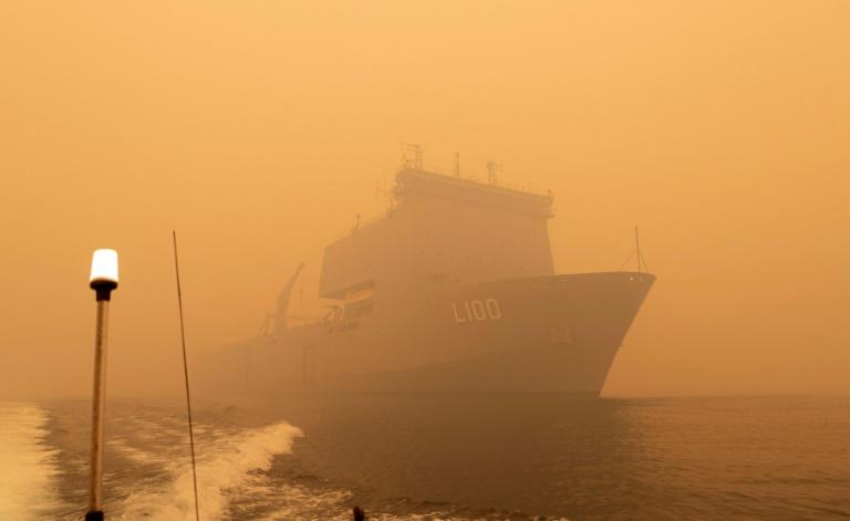 The Royal Australian Navy ship HMAS Choules sails amid heavy smoke off the coast of Mallacoota, Victoria state to assist in bushfire relief efforts