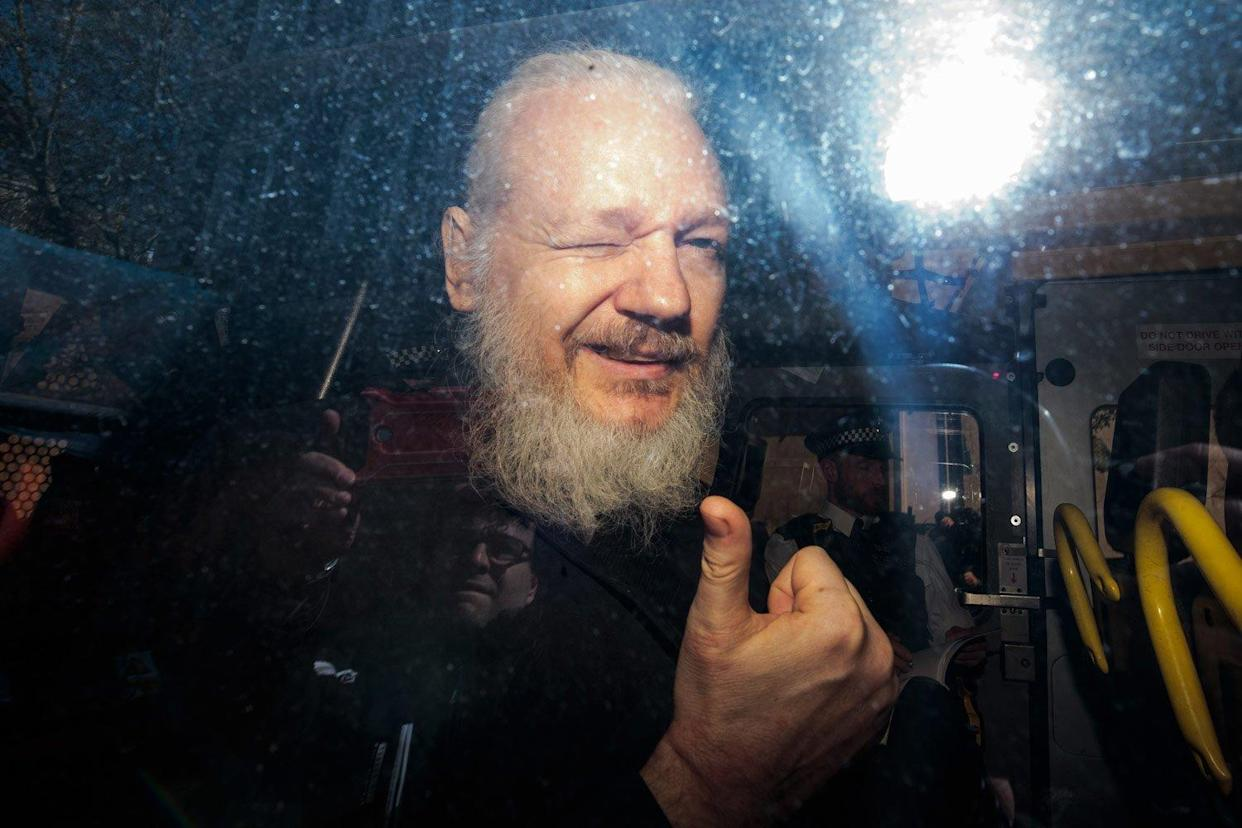 Julian Assange winks and sticks his thumb up for the cameras (Getty Images)