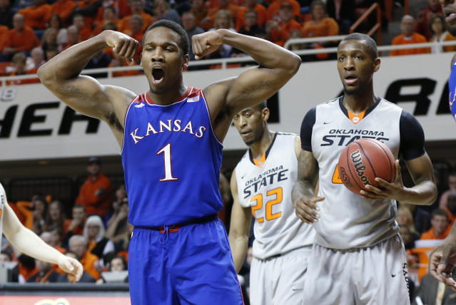 Kansas guard Wayne Selden Jr. (1) reacts to a basket in front of Oklahoma State wing Markel Brown (22) and post Kamari Murphy in the first half of an NCAA college basketball game in Stillwater, Okla., Saturday, March 1, 2014. (AP Photo/Sue Ogrocki)