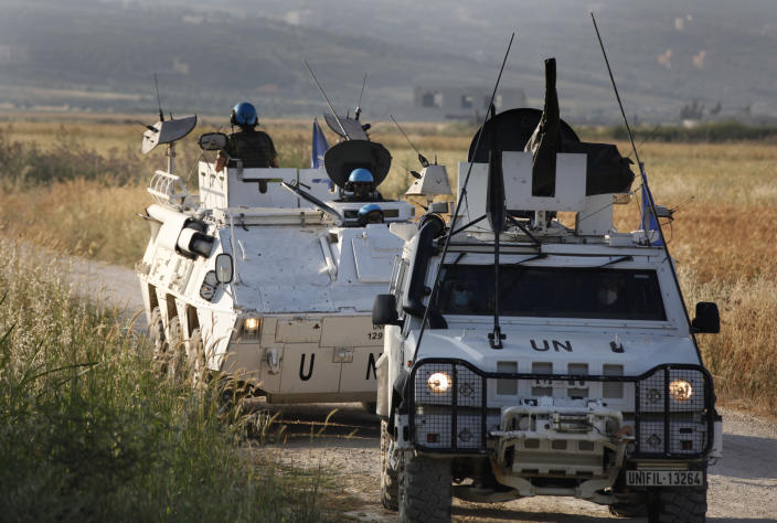 U.N peacekeepers patrol at the area where Hezbollah supporters hold a protest in solidarity with Palestinians amid an escalating Israeli military campaign in Gaza, on the Lebanese-Israeli border in front of the Israeli settlement of Metula, background, near the southern village of Kafr Kila, Lebanon, Friday, May 14, 2021. (AP Photo/Mohammed Zaatari)