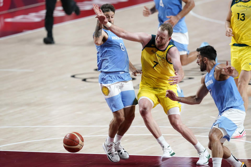 Australia's Joe Ingles (7) loses the ball between Argentina's Nicolas Laprovittola (8) and Facundo Campazzo, right, during a men's basketball quarterfinal round game at the 2020 Summer Olympics, Tuesday, Aug. 3, 2021, in Saitama, Japan. (AP Photo/Charlie Neibergall)