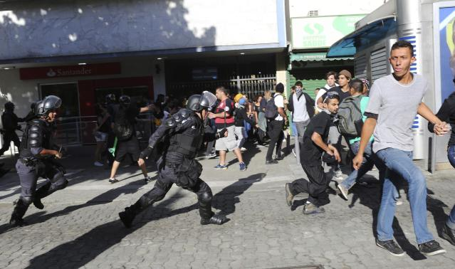 Policemen clash with demonstrators before the World Cup final match between Argentina and Germany in Rio de Janeiro July 13, 2014. REUTERS/Nacho Doce (BRAZIL - Tags: SPORT SOCCER WORLD CUP POLITICS CIVIL UNREST)