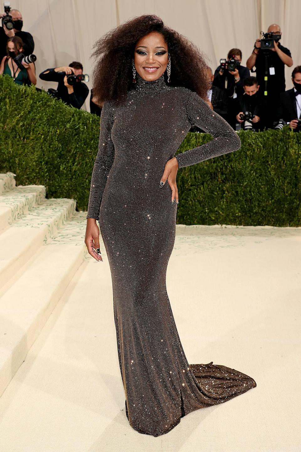 <p>in a high-neck, backless gold-and-black glittering gown.</p>