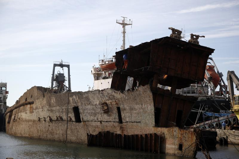 "In this Monday, Nov. 5, 2018 photo, in a shipyard of Perama, west of Athens, workers cut up the rusted remains of a ferry that was recovered after spending years as a shipwreck. Dozens of abandoned cargo and passenger ships lie semi-submerged or completely sunken around the Gulf of Elefsina, near Greece's major port of Piraeus. Now authorities are beginning to remove the dilapidated ships. Some of them have been there for decades, leaking hazards like oil into the environment and creating a danger to modern shipping. One expert calls the abandoned ships ""an environmental bomb."" (AP Photo/Thanassis Stavrakis)"