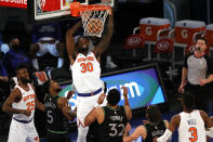 Julius Randle, center, of the New York Knicks dunks as Malik Beasley, left, and Karl-Anthony Towns, right, of the Minnesota Timberwolves look on during the first half of an NBA basketball game Sunday, Feb. 21, 2021, in New York. (Sarah Stier/Pool Photo via AP)