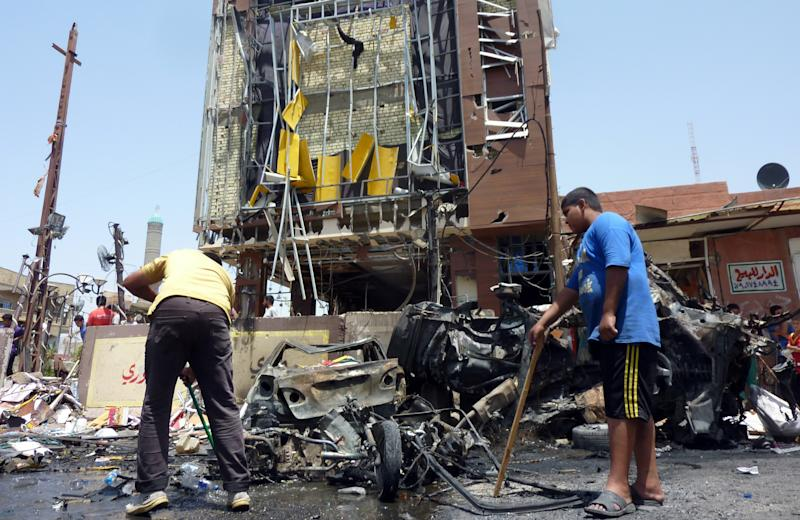Iraqi men clear the debris at the scene of a car bomb in the Sadr City district of Baghdad, on August 1, 2014 (AFP Photo/Ali Al-Saadi)