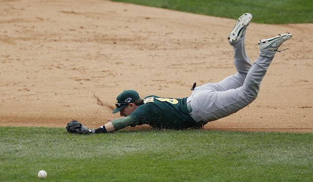Oakland Athletics shortstop Jed Lowrie dives but is unable to stop the single by Detroit Tigers' Prince Fielder during the sixth inning of Game 3 of an American League baseball division series in Detroit, Monday, Oct. 7, 2013. (AP Photo/Charles Rex Arbogast)