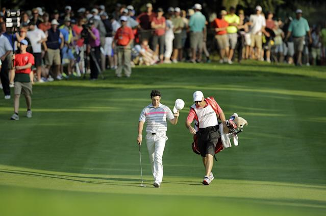 Rory McIlroy tips his hat as he walks down the 18th fairway with caddie J.P. Fitzgerald during the final round of the Bridgestone Invitational golf tournament Sunday, Aug. 3, 2014, at Firestone Country Club in Akron, Ohio. McIlroy's 15-under par total beat Sergio Garcia by two shots. (AP Photo/Mark Duncan)