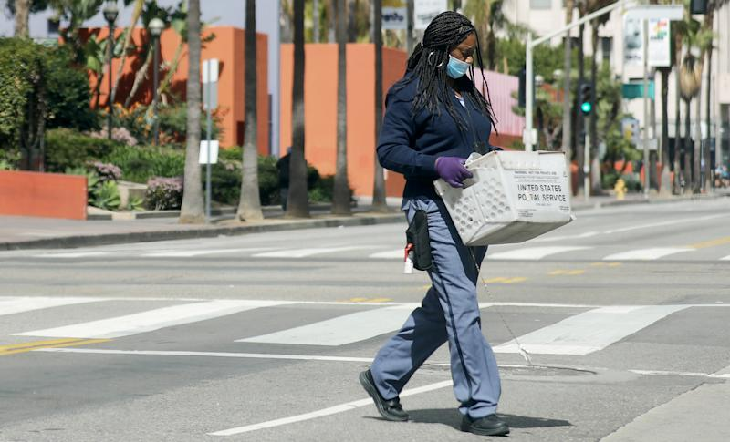 LOS ANGELES, CALIFORNIA - MARCH 24: A U.S.Postal Service worker wears a face mask and gloves while crossing a downtown street as the coronavirus pandemic continues on March 24, 2020 in Los Angeles, California. California Governor Gavin Newsom issued a 'stay at home' order for California's 40 million residents in order to slow the spread of COVID-19. (Photo by Mario Tama/Getty Images)