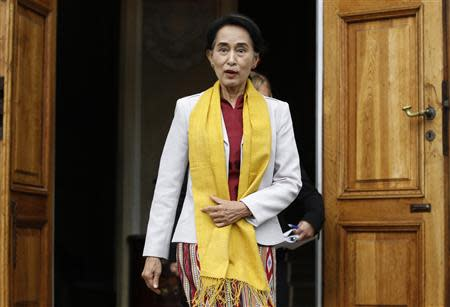 Myanmar's opposition leader Aung San Suu Kyi reacts after seeing photographers waiting for her after her meeting with Poland's former president Lech Walesa (not pictured) at Myslewicki Palace in Warsaw September 12, 2013. REUTERS/Kacper Pempel