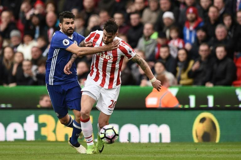 Chelsea's Diego Costa (L) fights for the ball with Stoke City's Geoff Cameron during their English Premier League match, at the Bet365 Stadium in Stoke-on-Trent, on March 18, 2017
