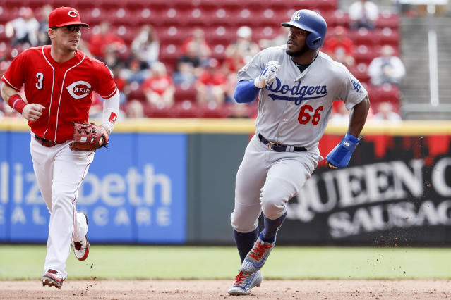 Los Angeles Dodgers' Yasiel Puig (66) runs to third on a double hit by Joc Pederson off Cincinnati Reds starting pitcher Anthony DeSclafani in the fifth inning of a baseball game, Wednesday, Sept. 12, 2018, in Cincinnati. (AP Photo/John Minchillo)