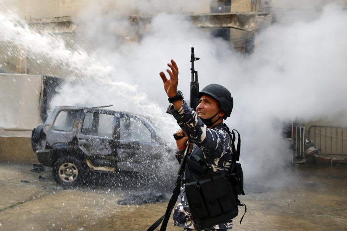 A Lebanese policeman gestures to firefighters as they extinguish a police car that was set on fire by anti-government protesters, in the northern city of Tripoli, Lebanon, Tuesday, April 28, 2020. Hundreds of angry Lebanese took part Tuesday in the funeral of a young man killed in riots overnight in Tripoli that were triggered by the crash of Lebanon's national currency that sent food prices soaring. (AP Photo/Bilal Hussein)