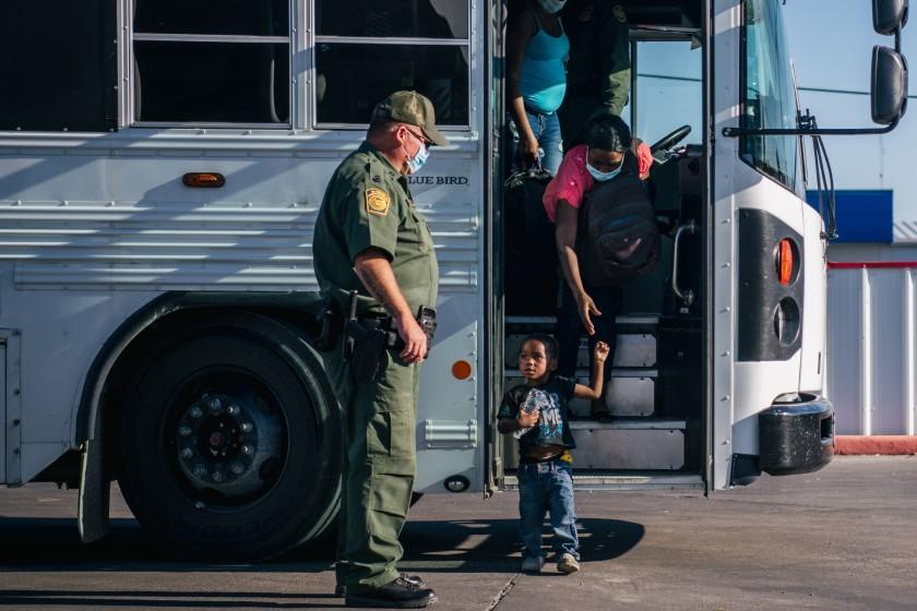 DEL RIO, TEXAS - SEPTEMBER 22: Migrants exit a Border Patrol bus and prepare to be received by the Val Verde Humanitarian Coalition after crossing the Rio Grande on September 22, 2021 in Del Rio, Texas. Thousands of immigrants, mostly from Haiti, seeking asylum have crossed the Rio Grande into the United States. Families are living in makeshift tents under the international bridge while waiting to be processed into the system. U.S. immigration authorities have been deporting planeloads of migrants directly to Haiti while others have crossed the Rio Grande back into Mexico. (Photo by Brandon Bell/Getty Images)