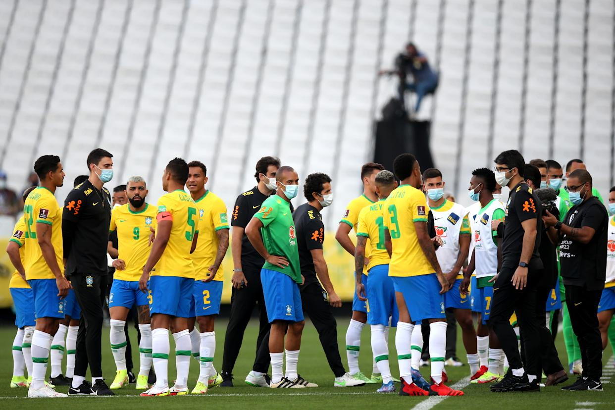Players of Brazil talk as the match is delayed by Brazilian health authorities.