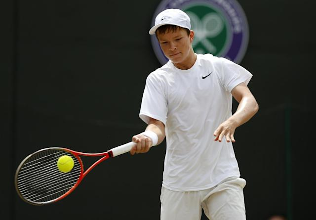 Stefan Kozlov of the U.S. plays a return to Noah Rubin of the U.S. during their boys' singles final at the All England Lawn Tennis Junior Championships at Wimbledon, London, Sunday July 6, 2014. (AP Photo/Sang Tan)