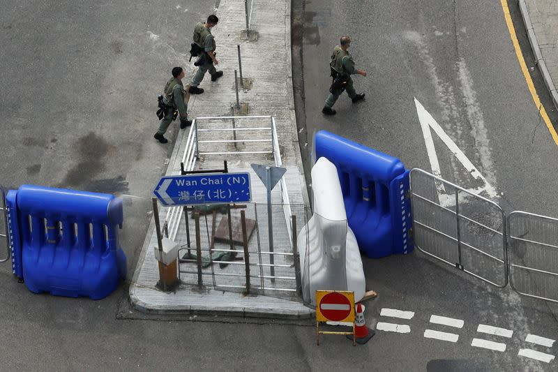 Riot police officers walk past a barricade as a second reading of a controversial national anthem law takes place in Hong Kong