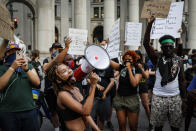 Protesters gather at an encampment outside City Hall, Tuesday, June 30, 2020, in New York. New York City lawmakers are holding a high-stakes debate on the city budget as activists demand a $1 billion shift from policing to social services and the city grapples with multibillion-dollar losses because of the coronavirus pandemic. (AP Photo/John Minchillo)