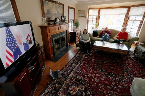 PHOTO: Lally Doerrer, left, and neighbors Douglas and Marlene Groll, watch Joe Biden during his Illinois virtual town hall, in her living room Friday, March 13, 2020, in Chicago. (Charles Rex Arbogast/AP, FILE)