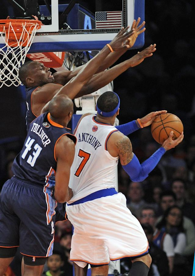 Charlotte Bobcats' Anthony Tolliver (43) and Bismack Biyombo guard New York Knicks' Carmelo Anthony (7) during the fourth quarter of an NBA basketball game, Friday, Jan. 24, 2014, at Madison Square Garden in New York. Anthony scored 62 points as the Knicks defeated the Bobcats 125-96. (AP Photo/Bill Kostroun)