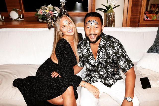 """<p>Teigen rang in 2021 with her husband, John Legend, <a href=""""https://www.instagram.com/p/CJfDziRhUoK/"""" rel=""""nofollow noopener"""" target=""""_blank"""" data-ylk=""""slk:captioning a smiling photo"""" class=""""link rapid-noclick-resp"""">captioning a smiling photo</a> of the pair, """"mom and dad wishing you a happy, healthy and beautiful new year blessed with the purest joys and most positive ~*v i b e s*~""""</p>"""