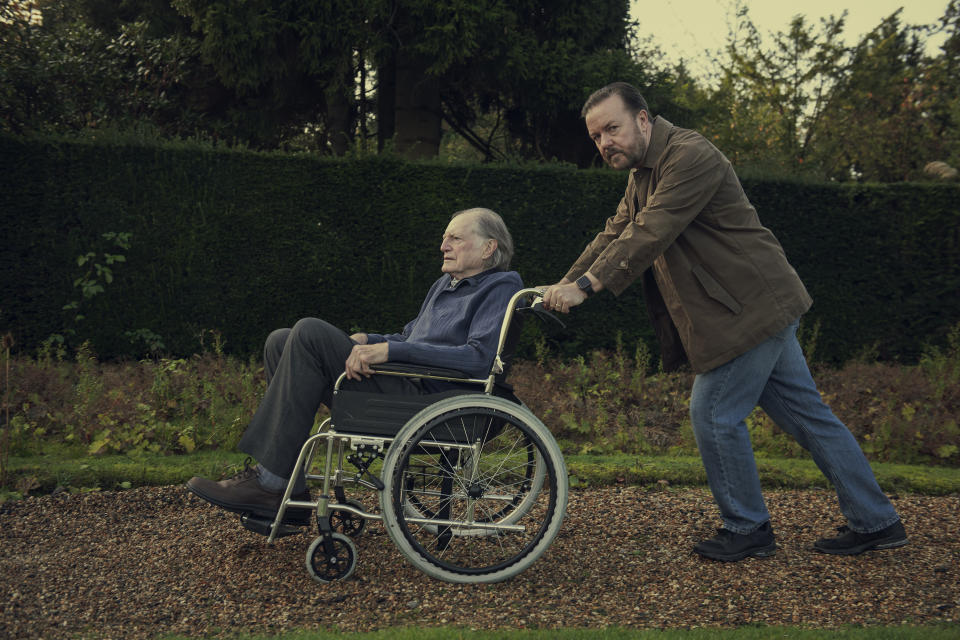 Ricky Gervais pushes David Bradley in a wheelchair in this still from <i>After Life</i>. (Netflix)