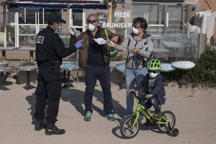A French police officer checks the documents of a family on a beach in Marseille. France has extended its nationwide lockdown measures. (AP)